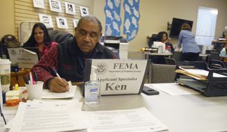 In this March 1, 2019 photo, Federal Emergency Management Agency applicant specialist Ken Sutton fills out paperwork at the Eagle River FEMA Disaster Recovery Center at Community Covenant Church in Eagle River, Alaska. At a small office in an Eagle River church, nearly a dozen federal employees are working to both mitigate problems and manage expectations of those seeking help after the Nov. 30, 2018 earthquake. They're the government, and they're here to help. (Matt Tunseth/Chugiak-Eagle River Star via AP)