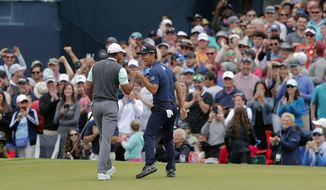 Tiger Woods, left, and Kevin Na share a laugh after putting out on the 17th green during the third round of The Players Championship golf tournament Saturday, March 16, 2019, in Ponte Vedra Beach, Fla. (AP Photo/Gerald Herbert)
