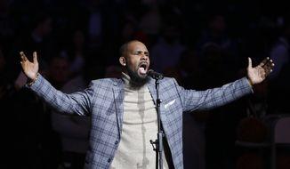 FILE - In this Nov. 17, 2015, file photo, musical artist R. Kelly performs the national anthem before an NBA basketball game between the Brooklyn Nets and the Atlanta Hawks in New York.  The dilemma of separating the sides of R. Kelly, who faces 10 counts of aggravated sexual abuse, now confronts millions who listen to or perform his music.  (AP Photo/Frank Franklin II, File)