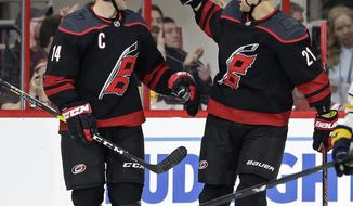 Carolina Hurricanes' Justin Williams (14) is congratulated by Nino Niederreiter (21), of the Czech Republic, following Williams' goal against the Buffalo Sabres during the second period of an NHL hockey game in Raleigh, N.C., Saturday, March 16, 2019. (AP Photo/Gerry Broome)