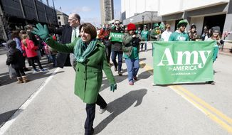 2020 Democratic presidential candidate Sen. Amy Klobuchar waves as she walks in the St. Patrick's Day Parade, Sunday, March 17, 2019, in Cedar Rapids, Iowa. (AP Photo/Charlie Neibergall)