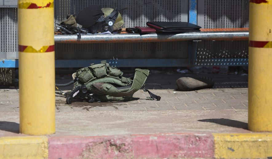 A vest of an Israeli soldier is seen on the ground at the scene of an attack near the West Bank Jewish settlement of Ariel, Sunday, March 17, 2019.The Israeli military says a Palestinian killed an Israeli and seriously wounded two others in a West Bank shooting and stabbing spree before fleeing and setting off a massive manhunt.(AP Photo/Sebastian Scheiner)