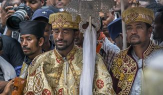 A priest cries at a mass funeral at the Holy Trinity Cathedral in Addis Ababa, Ethiopia Sunday, March 17, 2019. Thousands of Ethiopians have turned out to a mass funeral ceremony in the capital one week after the Ethiopian Airlines plane crash. Officials have begun delivering bags of earth to family members of the 157 victims of the crash instead of the remains of their loved ones because the identification process is going to take such a long time. (AP Photo/Mulugeta Ayene)