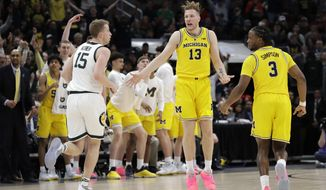 Michigan's Ignas Brazdeikis (13) reacts after shooting a 3-point basket during the first half of an NCAA college basketball championship game against Michigan State in the Big Ten Conference tournament, Sunday, March 17, 2019, in Chicago. (AP Photo/Nam Y. Huh)