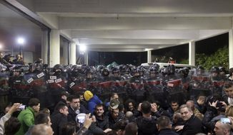 Protesters sit in front of a riot police cordon at an entrance to the state-run TV headquarters in Belgrade, Serbia, Saturday, March 16, 2019. Demonstrators protesting the autocratic rule of Serbian President Aleksandar Vucic burst into the state-run TV headquarters in Belgrade on Saturday to denounce a broadcaster whose reporting they consider highly biased. (AP Photo/Marko Drobnjakovic)