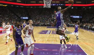 Sacramento Kings guard De'Aaron Fox, right, goes to the basket as Chicago Bulls forward Lauri Markkanen (24) watches during the first half of an NBA basketball game Sunday, March 17, 2019, in Sacramento, Calif. (AP Photo/Rich Pedroncelli)