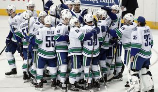 The Vancouver Canucks gather on the ice to celebrate with Josh Leivo, far right in group, after Leivo scored a shootout goal against the Dallas Stars in an NHL hockey game in Dallas, Sunday, March 17, 2019. The Canucks won 3-2. (AP Photo/Tony Gutierrez)