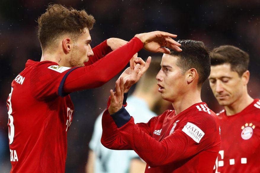Bayern's James, right, celebrates with teammate Leon Goretzka after scoring during the German Bundesliga soccer match between FC Bayern Munich and 1. FSV Mainz 05 in Munich, Germany, Sunday, March 17, 2019. (AP Photo/Matthias Schrader)
