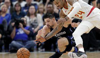 Orlando Magic's Nikola Vucevic, left, and Atlanta Hawks' Kent Bazemore (24) go after a loose ball during the first half of an NBA basketball game, Sunday, March 17, 2019, in Orlando, Fla. (AP Photo/John Raoux)