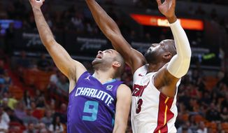 Charlotte Hornets guard Tony Parker (9) goes up to shoot against Miami Heat guard Dwyane Wade (3) during the first half of an NBA basketball game, Sunday, March 17, 2019, in Miami. (AP Photo/Wilfredo Lee)
