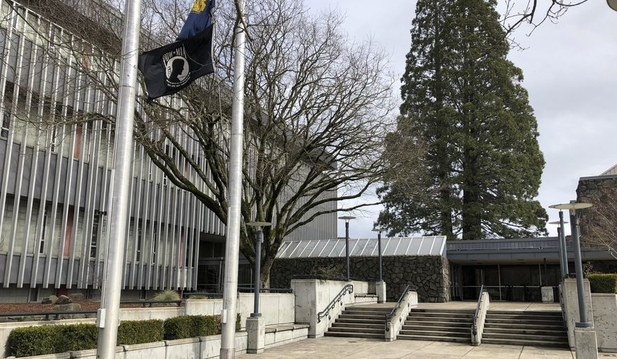 In this photo taken March 7, 2019, flags, including a POW/MIA flag, flap in a breeze in front of the Lane County Circuit Court building where the Veterans Treatment Court is held in Eugene, Ore. Military veterans who are struggling with addiction and have tangled with the law are being given a second chance in an Oregon courtroom. But the Veterans Treatment Court and 40 other specialty courts in Oregon are at risk of losing their federal funding unless the state enforces federal immigration policies. (AP Photo/Andrew Selsky)