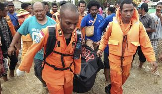 In this photo provided by National Search and Rescue Agency, or BASARNAS, the agency's personnel and police carry the body of flood victim at Sentani, Papua Province, Indonesia, Sunday, March 17, 2019. Flash flood and mudslides triggered by days of torrential downpours tore through mountainside villages in Indonesia's easternmost province, killing dozens of people, disaster officials said Sunday. (BASARNAS via AP)