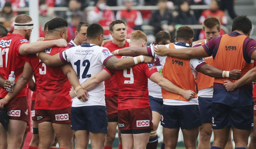 Players offer a silent prayer for victims of a mass shooting at New Zealand before their Super Rugby match between Sunwolves and Reds in Tokyo, Saturday, March 16, 2019. (AP Photo/Koji Sasahara)