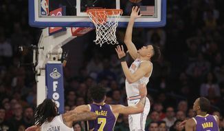 New York Knicks' Kevin Knox, top, scores during the first half of an NBA basketball game against the Los Angeles Lakers, Sunday, March 17, 2019, in New York. (AP Photo/Seth Wenig)