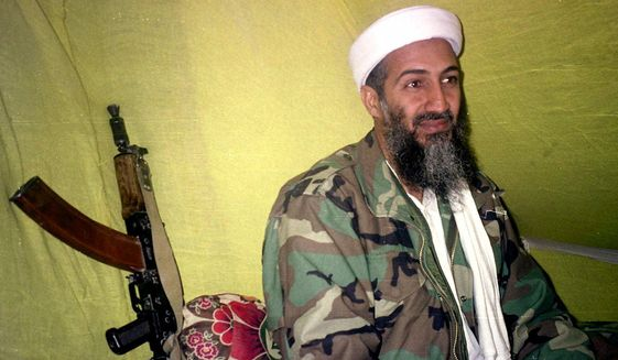 Then-al Qaeda leader Osama Bin Laden speaks to a selected group of reporters in mountains of Helmand province in southern Afghanistan, Dec. 24, 1998. (AP Photo/Rahimullah Yousafzai) ** FILE **