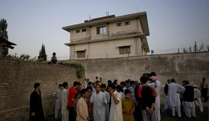 In this May 3, 2011, file photo, local residents gather outside a house where al Qaeda leader Osama bin Laden was killed in Abbottabad, Pakistan. (AP Photo/B.K.Bangash, File)