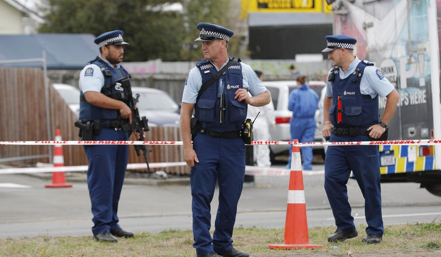 Police officials stand guard as religious representatives perform a special blessing ceremony on the site of Friday's shooting outside the Linwood mosque in Christchurch, New Zealand, Monday, March 18, 2019. Three days after Friday's attack, New Zealand's deadliest shooting in modern history, relatives were anxiously waiting for word on when they can bury their loved ones. (AP Photo/Vincent Thian)
