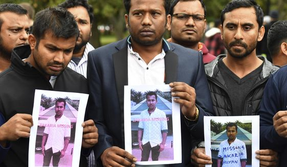 Friends of a missing man Zakaria Bhuiyan hold up photos of him outside a refuge center in Christchurch, Sunday, March 17, 2019. The live-streamed attack by an immigrant-hating white nationalist killed dozens of people as they gathered for weekly prayers in Christchurch.  (Mick Tsikas/AAP Image via AP)