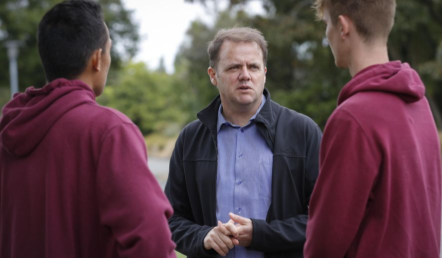Cashmere High School principal Mark Wilson, center, speaks with his students at the school in Christchurch, New Zealand, Sunday, March 17, 2019. Three students from the high school were at the Al Noor Mosque for Friday prayers when an attacker burst in as part of a rampage that left 50 dead across the New Zealand city of Christchurch. When classes resume Monday, none will be there.  Two of the students are presumed dead and the third is in the hospital with gunshot wounds.(AP Photo/Vincent Thian)