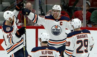 Edmonton Oilers center Connor McDavid (97) smiles as he celebrates his game-winning goal against the Arizona Coyotes with Zack Kassian (44), Oscar Klefbom (77) and Leon Draisaitl (29) during overtime of an NHL hockey game Saturday, March 16, 2019, in Glendale, Ariz. The Oilers won 3-2. (AP Photo/Ross D. Franklin)