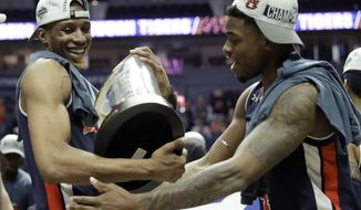Auburn's Horace Spencer, left, holds the trophy as he celebrates with teammate Malik Dunbar after defeating Tennessee in the championship game of the NCAA Southeastern Conference basketball tournament Sunday, March 17, 2019, in Nashville, Tenn. Auburn won 84-64. (AP Photo/Mark Humphrey)