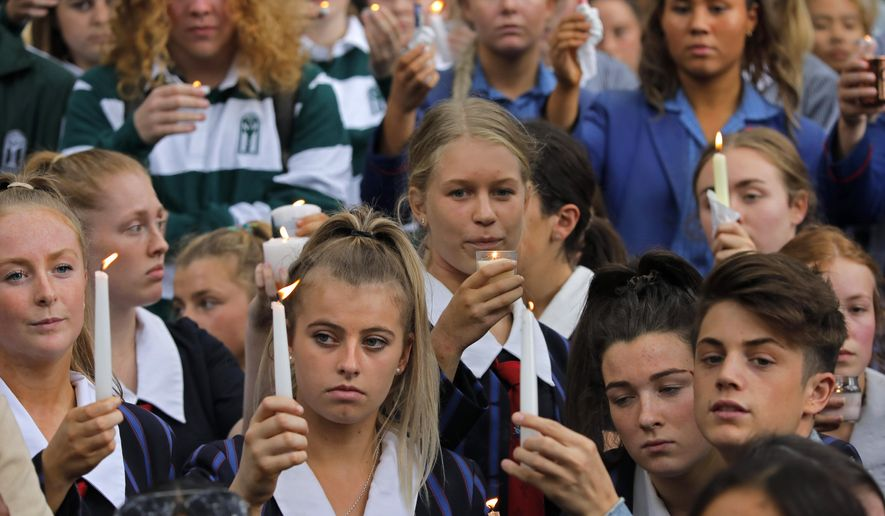 Students raise candles as they gather for a vigil to commemorate victims of Friday's shooting, outside the Al Noor mosque in Christchurch, New Zealand, Monday, March 18, 2019. Three days after Friday's attack, New Zealand's deadliest shooting in modern history, relatives were anxiously waiting for word on when they can bury their loved ones.(AP Photo/Vincent Yu)