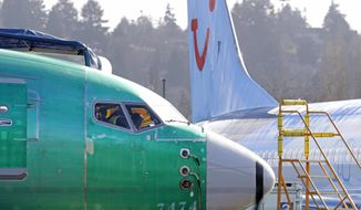 "FILE- In this March 13, 2019, file photo people work in the flight deck of a Boeing 737 MAX 8 airplane being built for TUI Group parked next to another MAX 8 also designated for TUI at Boeing Co.'s Renton Assembly Plant in Renton, Wash. U.S. prosecutors are looking into the development of Boeing's 737 Max jets, a person briefed on the matter revealed Monday, the same day French aviation investigators concluded there were ""clear similarities"" in the crash of an Ethiopian Airlines Max 8 last week and a Lion Air jet in October. (AP Photo/Ted S. Warren, file)"
