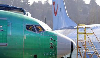 "In this March 13, 2019, file photo, people work in the flight deck of a Boeing 737 MAX 8 airplane being built for TUI Group parked next to another MAX 8 also designated for TUI at Boeing Co.'s Renton Assembly Plant in Renton, Wash. U.S. prosecutors are looking into the development of Boeing's 737 Max jets, a person briefed on the matter revealed Monday, the same day French aviation investigators concluded there were ""clear similarities"" in the crash of an Ethiopian Airlines Max 8 last week and a Lion Air jet in October. (AP Photo/Ted S. Warren, file)"