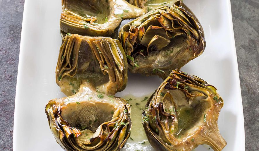 """This undated photo provided by America's Test Kitchen in March 2019 shows Roasted Artichokes With Vinaigrette in Brookline, Mass. This recipe appears in the cookbook """"Nutritious Delicious."""" (Daniel J. van Ackere/America's Test Kitchen via AP)"""