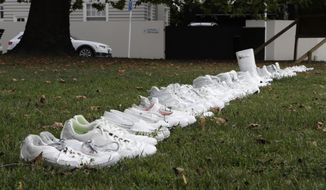 Fifty pairs of white shoes line up as a memorial to the victims of Friday March 15 mass mosque shootings in front of a church in Christchurch, New Zealand, Tuesday, March 19, 2019. Four days after Friday's attack, New Zealand's deadliest shooting in modern history, relatives were anxiously waiting for word on when they can bury their loved ones. (AP Photo/Mark Baker)