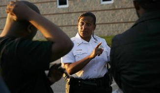 James Boyd, left, and Rocky Hines, right, speak with Portsmouth Police Chief Tonya Chapman at Norcom High School in Portsmouth, Va. Chapman, the first black woman to lead a municipal police force in Virginia, abruptly resigned Monday, March 18, 2019 from her police chief job in Portsmouth. Chapman had led the Portsmouth Police Department for three years.(Kristen Zeis/The Virginian-Pilot via AP)