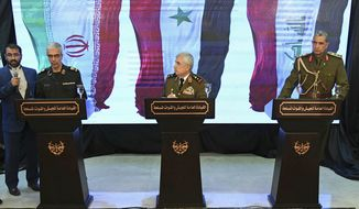 """In this photo released by the Syrian official news agency SANA, Iran's Chief of Staff of Armed Forces, Maj. Gen. Mohammad Hossein Bagheri, left, speaks during a press conference with Syria's defense minister Gen. Ali Ayoub, center, and Iraqi army commander, Gen. Osman Ghanemi in Damascus, Syria, Monday, March 18, 2019. Syria's defense minister slammed what he called the """"illegitimate"""" U.S. military presence in his country, vowing that Syria has a right to self-defense. (SANA via AP)"""