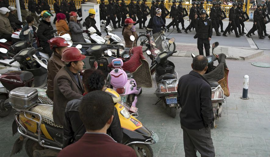 "FILE - In this Nov. 5, 2017, file photo, residents watch a convoy of security personnel armed with batons and shields patrol through central Kashgar in western China's Xinjiang region. China says on Monday, March 18, 2019 it has arrested nearly 13,000 people it describes as terrorists in the traditionally Islamic region of Xinjiang since 2014 and broken up hundreds of ""terrorist gangs."" The figures were included in a government report on the situation in the restive northwestern territory that seeks to respond to growing criticism over the internment of an estimated 1 million members of the Uighur (WEE-gur) and other predominantly Muslim ethnic groups. (AP Photo/Ng Han Guan, File)"