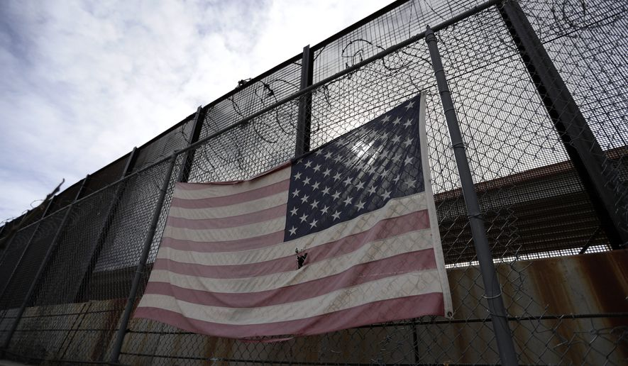 In this Monday, Jan. 21, 2019, photo, a U.S. flag hangs on a border barrier in El Paso, Texas. Such barriers have been a part of El Paso for decades and are currently being expanded, even as the fight over President Donald Trump's desire to wall off the entire U.S.-Mexico border has sparked the longest government shutdown in the nation's history.(AP Photo/Eric Gay)