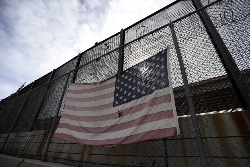 In this Monday, Jan. 21, 2019, photo, a U.S. flag hangs on a border barrier in El Paso, Texas. (AP Photo/Eric Gay) **FILE**