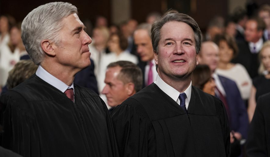 In this Feb. 5, 2019, file photo, Supreme Court Associate Justices Neil Gorsuch, left, and Brett Kavanaugh watch as President Donald Trump arrives to give his State of the Union address to a joint session on Congress at the Capitol in Washington. (Doug Mills/The New York Times via AP, Pool)