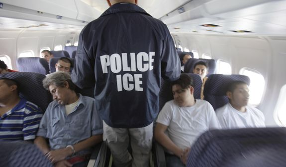 In this May 25, 2010 file photo, an Immigration and Customs Enforcement agent walks down the aisle among shackled Mexican immigrants a boarded a U.S. Immigration and Customs Enforcement charter jet for deportation in the air between Chicago, Il. and Harlingen, Texas. (Associated Press)