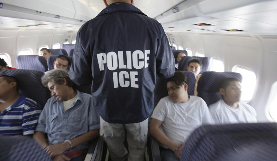 In this May 25, 2010, file photo, an Immigration and Customs Enforcement agent walks down the aisle among shackled Mexican immigrants aboard a U.S. Immigration and Customs Enforcement charter jet for deportation, flying between Chicago, Il., and Harlingen, Texas. (Associated Press) ** FILE **