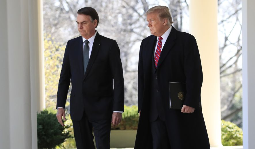 President Donald Trump walks with visiting Brazilian President Jair Bolsonaro along the Colonnade of the White House, Tuesday, March 19, 2019, in Washington. (AP Photo/Manuel Balce Ceneta)