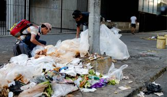 People check a garbage pile for food, in Caracas, Venezuela, Monday, March 18, 2019. Venezuelans are facing a severe economic and political crisis as President Nicolas Maduro has remained in power despite heavy pressure from the United States and other countries arrayed against him, managing to retain the loyalty of most of Venezuelas military leaders. (AP Photo/Natacha Pisarenko)