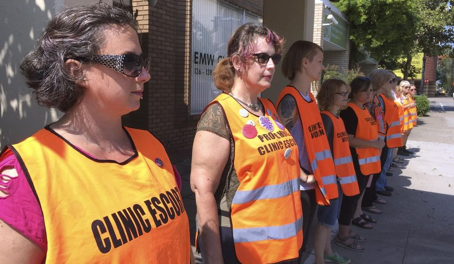 FILE - In this July 17, 2017 file photo, escort volunteers line up outside the EMW Women's Surgical Center in Louisville, Ky. Kentucky's Republican governor has signed a measure putting new restrictions on abortion, and his lawyers filed a response to a lawsuit already aimed at blocking it, Tuesday, March 19, 2019. Before Gov. Matt Bevin signed the measure, the American Civil Liberties Union challenged the legislation in a federal lawsuit. The new law bans abortion for women seeking to end their pregnancies because of the gender, race or disability of the fetus. (AP Photo/Dylan Lovan, File)