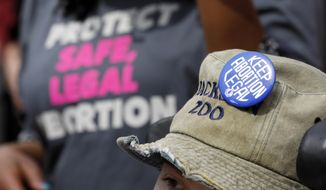 FILE -  In this March 14, 2019 file photograph, a Planned Parenthood supporter hosts an abortion rights button on her hat during a rally on the steps of the Capitol in Jackson, Miss. On Tuesday, March 19, 2019, Mississippi senators passed the final version of a bill that would ban most abortions once a fetal heartbeat can be detected, about six weeks into pregnancy. (AP Photo/Rogelio V. Solis, File)