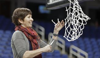 Notre Dame head coach Muffet McGraw cuts a piece of the net after her team defeated Louisville in an NCAA college basketball game in the championship of the Atlantic Coast Conference women's tournament in Greensboro, N.C., Sunday, March 10, 2019. (AP Photo/Chuck Burton)