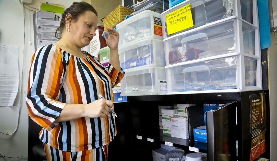 In this Friday, March 15, 2019, photo, Laura Levine prepares to dispense drugs at Vocal NY, an organization that works with addicts, where she is the health educator and coordinator for the opioid reversal drug Narcan, in the Brooklyn borough of New York. New York state is considering providing medication-assisted treatment to all prison and jail inmates struggling with opioid addiction. (AP Photo/Bebeto Matthews)