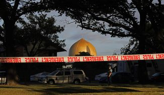 A police officer stands guard in front of the Masjid Al Noor mosque in Christchurch, New Zealand, Sunday, March 17, 2019, where one of two mass shootings occurred. New Zealand's stricken residents reached out to Muslims in their neighborhoods and around the country on Saturday, to show kindness to a community in pain as a 28-year-old white supremacist stood silently before a judge, accused in mass shootings at two mosques that left dozens of people dead. (AP Photo/Vincent Yu)