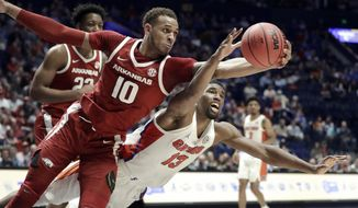 Florida's Kevarrius Hayes (13) and Arkansas's Daniel Gafford (10) scramble for the ball in the second half of an NCAA college basketball game at the Southeastern Conference tournament Thursday, March 14, 2019, in Nashville, Tenn. Florida won 66-50. (AP Photo/Mark Humphrey)