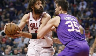 Chicago Bulls center Robin Lopez looks to shoot over Phoenix Suns forward Dragan Bender (35) during the second half of an NBA basketball game, Monday, March 18, 2019, in Phoenix. (AP Photo/Matt York)