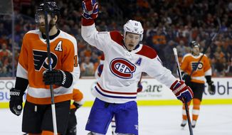 Montreal Canadiens' Brendan Gallagher, center, celebrates past Philadelphia Flyers' Sean Couturier, left, after scoring a goal during the first period of an NHL hockey game, Tuesday, March 19, 2019, in Philadelphia. (AP Photo/Matt Slocum)