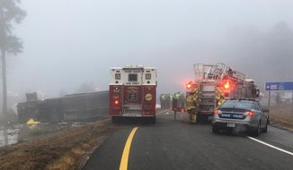 This photo provided by Virginia State Police emergency responders at the scene after a charter bus overturned on an Interstate 95 exit near Kingwood, Va., Tuesday, March 19, 2019.  Virginia State Police said in a statement that the Tao's Travel Inc. bus with 57 people aboard overturned Tuesday morning in Prince George County near Kingwood while traveling from Florida to New York. (Virginia State Police via AP)