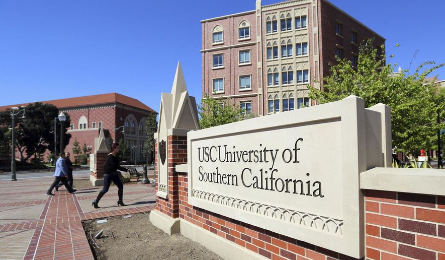 FILE - This Tuesday, March 12, 2019 file photo shows the University Village area of the University of Southern California in Los Angeles. The university says a review of students possibly connected to a college admissions bribery scandal could lead to expulsions. The university said in a statement Monday, March 18, 2019, it has placed holds on the accounts of those students, which prevents them from registering for classes or acquiring transcripts while their cases are under review. (AP Photo/Reed Saxon,File)